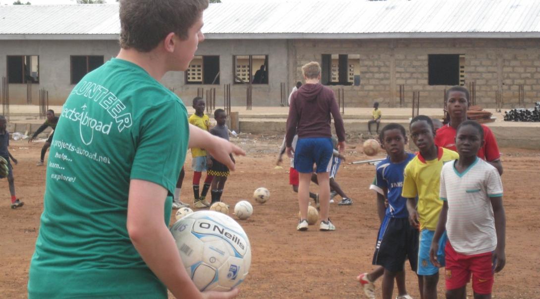 Entrenador voluntario de fútbol le da instrucciones a sus jugadores.